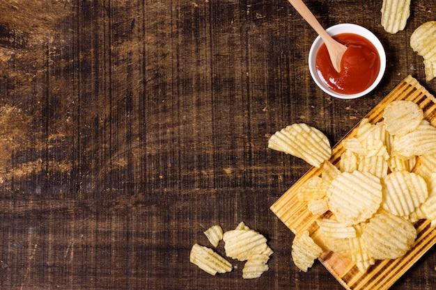Draufsicht auf kartoffelchips mit ketchup und kopierraum