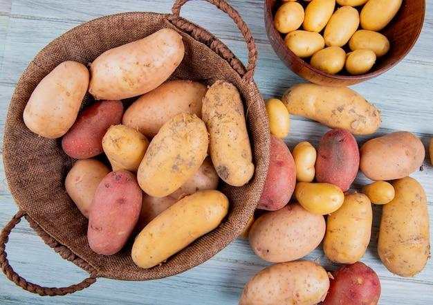Draufsicht auf kartoffeln im korb mit neuen in der schüssel und anderen von verschiedenen arten auf holzoberfläche