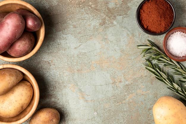 Draufsicht auf kartoffeln in schalen mit rosmarin und gewürzen