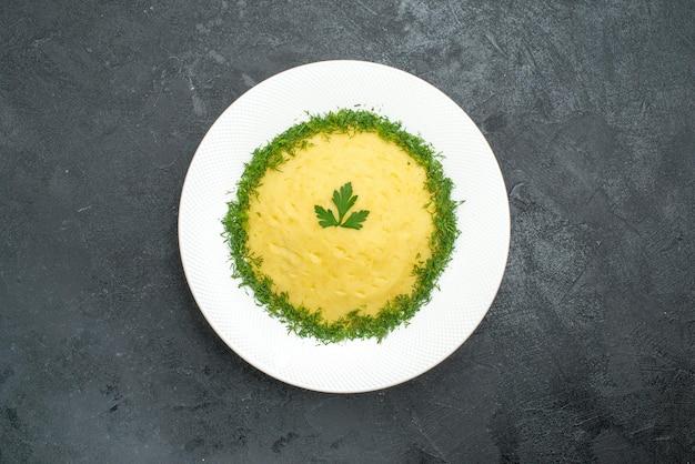 Draufsicht auf kartoffelpüree mit grün im teller auf grau