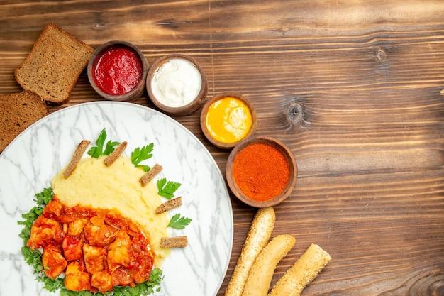 Draufsicht auf kartoffelpüree mit hähnchenscheiben, brot und gewürzen auf braunem tisch