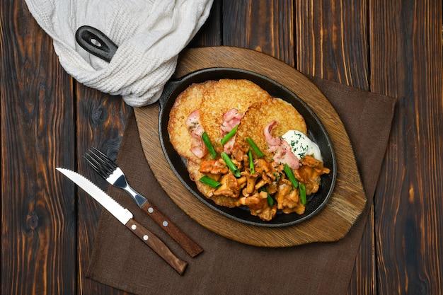 Draufsicht auf kartoffelpuffer mit pfifferlingen und schweinefleisch in der gusseisernen pfanne