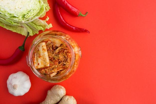 Draufsicht auf kimchi im glas und zutaten auf dem rot