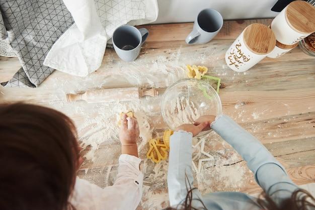 Draufsicht auf kinder, die lernen, mit speziell geformten instrumenten essen aus dem mehl zuzubereiten.