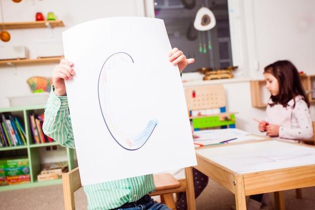 Draufsicht auf kinder im kindergarten lernen buchstaben und formen, die sie färben