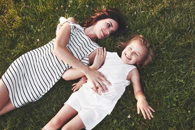 Draufsicht auf kinder und mutter, die sich auf das mit sonnenschein gefüllte gras legen und sich gegenseitig ansehen at