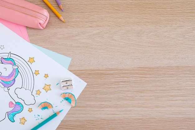 Draufsicht auf kinderschreibtisch mit zeichnungen und bleistiften