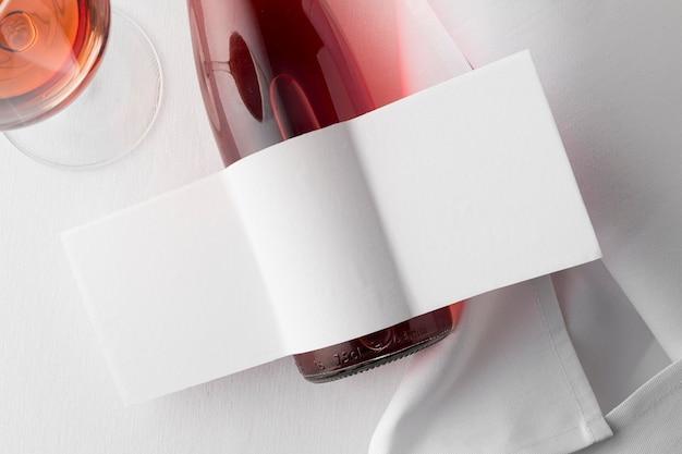Draufsicht auf klare weinflasche und glas mit leerem etikett