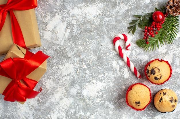Draufsicht auf kleine cupcakes süßigkeiten und tannenzweige dekorationszubehör und geschenke mit rotem band auf eisoberfläche