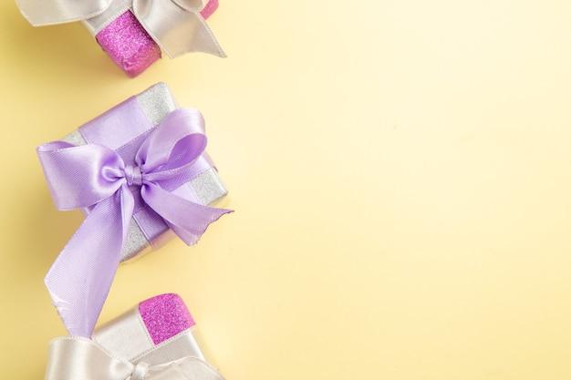 Draufsicht auf kleine geschenke auf hellgelber oberfläche