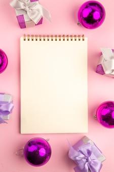 Draufsicht auf kleine geschenke mit weihnachtsbaumspielzeug und notizblock auf der rosa oberfläche