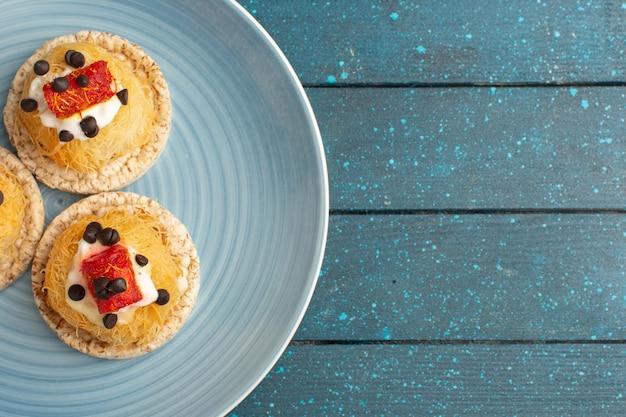 Draufsicht auf kleine köstliche cupcakes mit sahne und marmelade an der spitze