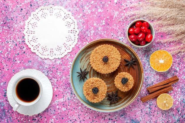 Draufsicht auf kleine köstliche kuchen mit hartriegeln und tee auf der hellrosa oberfläche