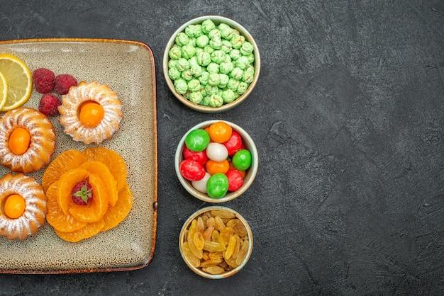 Draufsicht auf kleine kuchen mit zitronenscheiben, mandarinen und bonbons auf schwarz