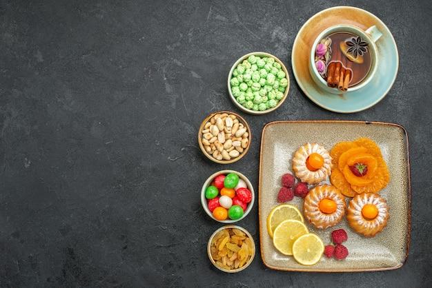 Draufsicht auf kleine leckere kuchen mit süßigkeiten, früchten und nüssen auf grau