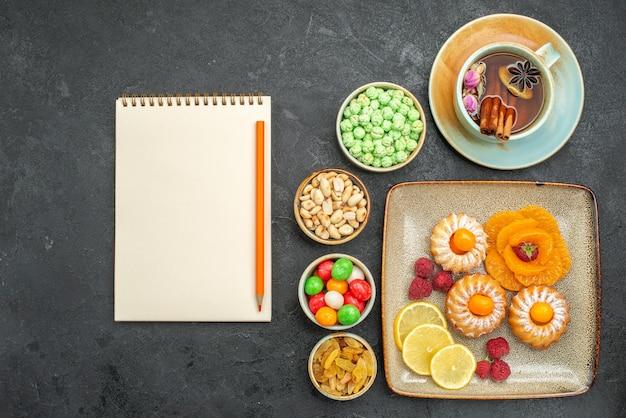 Draufsicht auf kleine leckere kuchen mit süßigkeiten, früchten und nüssen auf grauem tisch