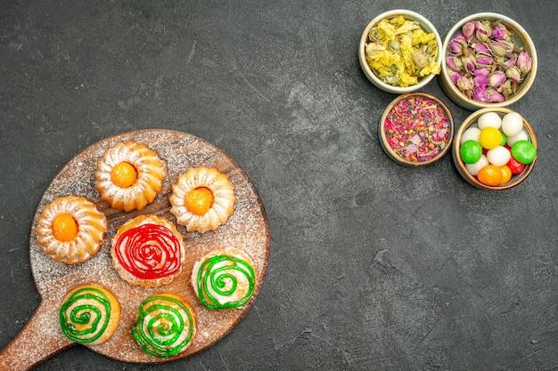 Draufsicht auf kleine leckere kuchen mit süßigkeiten und blumen auf dunkelheit