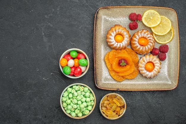 Draufsicht auf kleine leckere kuchen mit zitronenscheiben, mandarinen und bonbons auf dunkelheit
