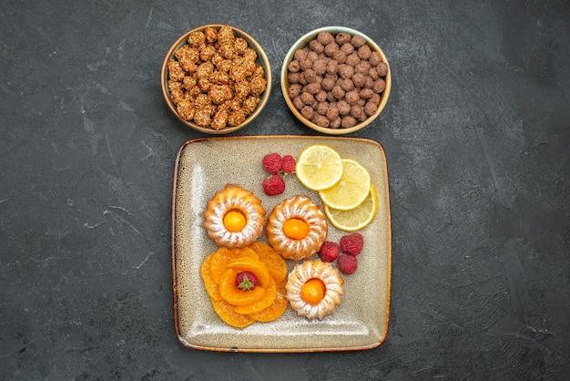 Draufsicht auf kleine leckere kuchen mit zitronenscheiben, mandarinen und bonbons auf grau