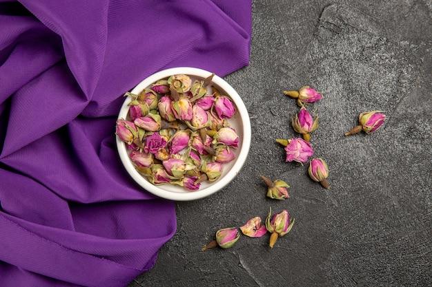 Draufsicht auf kleine lila blüten mit lila gewebe auf grau on