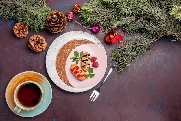 Draufsicht auf kleine süße kekse im gestalteten teller auf schwarzem lila