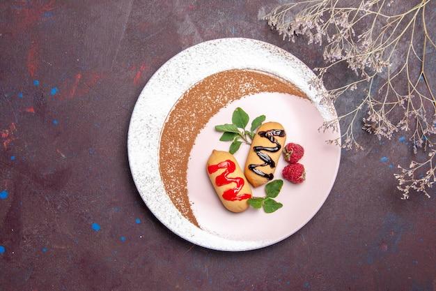 Draufsicht auf kleine süße kekse im inneren des tellers auf schwarz