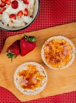 Draufsicht auf knusprige knäckebrote, die mit marmelade und erdbeeren auf schneidebrett mit haferflocken auf roter und weißer oberfläche verschmiert sind