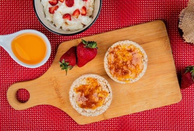 Draufsicht auf knusprige knäckebrote, die mit marmelade und erdbeeren auf schneidebrett mit haferflocken und geschmolzener butter auf roter und weißer oberfläche verschmiert sind