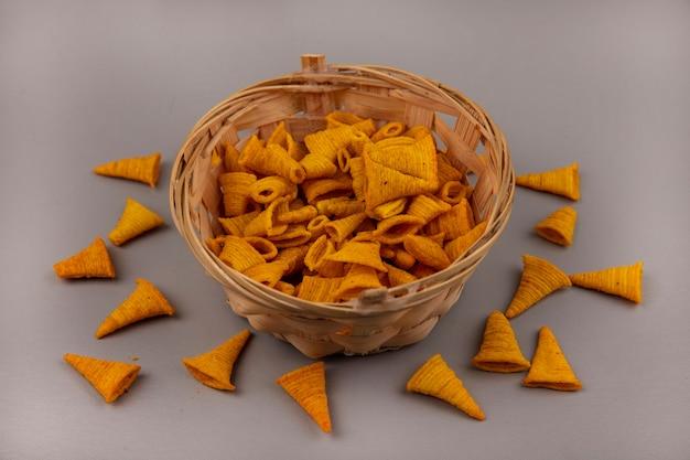 Draufsicht auf knusprige kornförmige gebratene maissnacks auf einem eimer mit chips lokalisiert