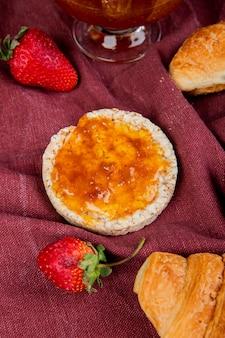 Draufsicht auf knuspriges knäckebrot und erdbeeren mit brötchen und marmelade auf bordo-stoffoberfläche