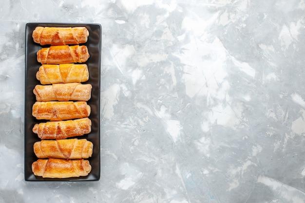 Draufsicht auf köstliche armreifen mit füllung innerhalb der schwarzen form auf leichtem, süßem zucker des gebäckkuchenplätzchens