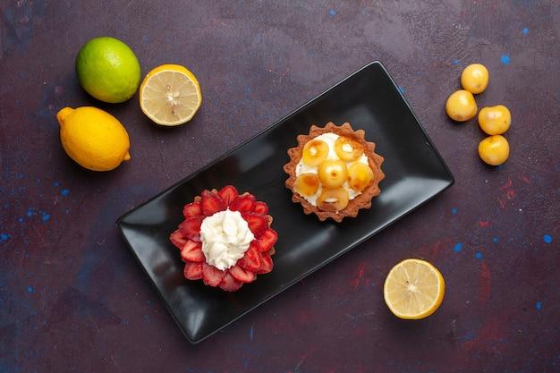 Draufsicht auf köstliche cremige kuchen innerhalb platte mit frischen zitronen auf der dunklen oberfläche