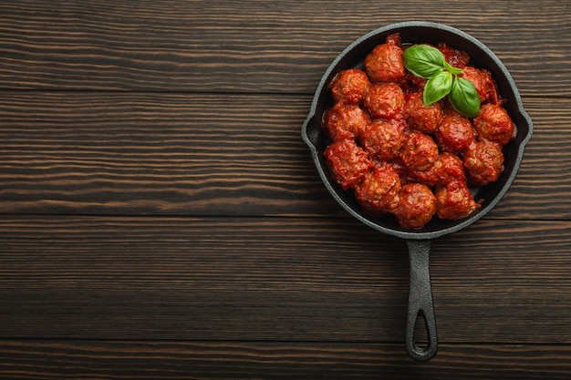 Draufsicht auf köstliche fleischbällchen mit tomatensauce und frischem basilikum in einer rustikalen vintage-pfanne aus gusseisen, serviert auf holzhintergrund. leckere hausgemachte frikadellen mit platz für text