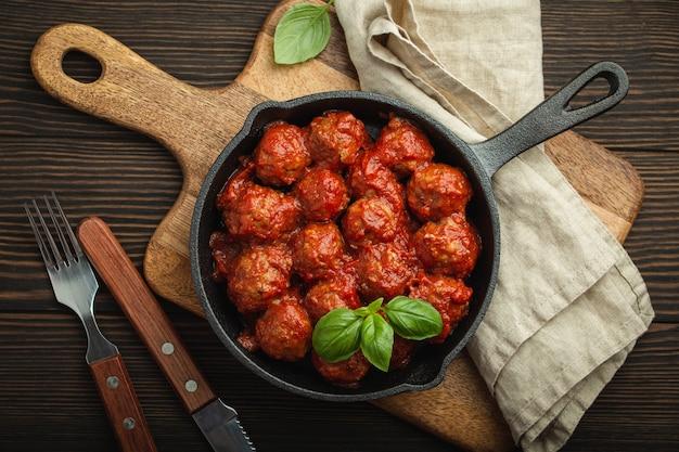 Draufsicht auf köstliche fleischbällchen mit tomatensauce und frischem basilikum in einer rustikalen vintage-pfanne aus gusseisen, serviert auf schneidebrett, holzhintergrund. leckere hausgemachte frikadellen