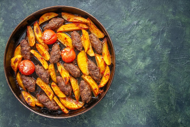 Draufsicht auf köstliche fleischkoteletts, die mit kartoffeln und tomaten auf der rechten seite auf grünem und schwarzem mischfarbhintergrund gebacken werden