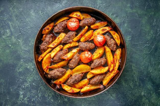 Draufsicht auf köstliche fleischkoteletts, die mit kartoffeln und tomaten auf grünem und schwarzem mischfarbhintergrund gebacken werden