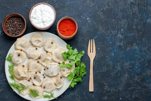 Draufsicht auf köstliche gebackene knödel innerhalb des tellers zusammen mit joghurt und grün auf dunkelgrauem, teigabendessenfleischkalorienmahlzeitnahrung