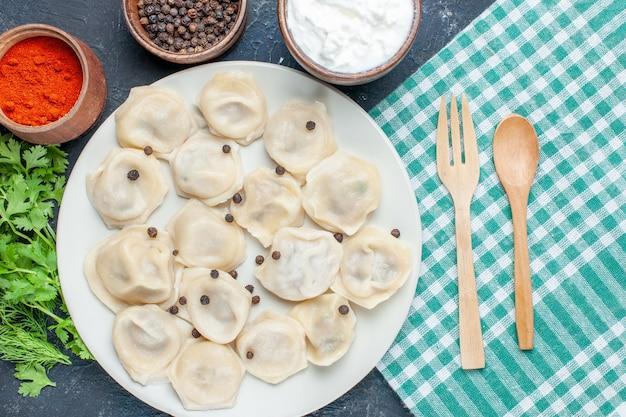 Draufsicht auf köstliche gebackene knödel innerhalb des tellers zusammen mit pfefferjoghurt und -grün auf dunklem schreibtisch, teigmahlzeit-abendessen-fleischkalorie