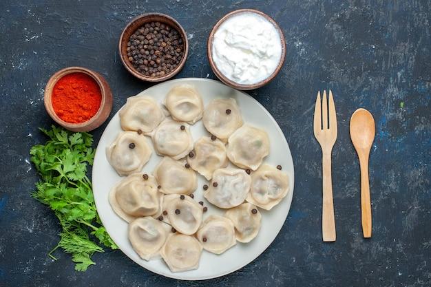 Draufsicht auf köstliche gebackene knödel innerhalb des tellers zusammen mit pfefferjoghurt und -grün auf dunklen, teigmahlzeitnahrungsmittel-abendessenfleischkalorien
