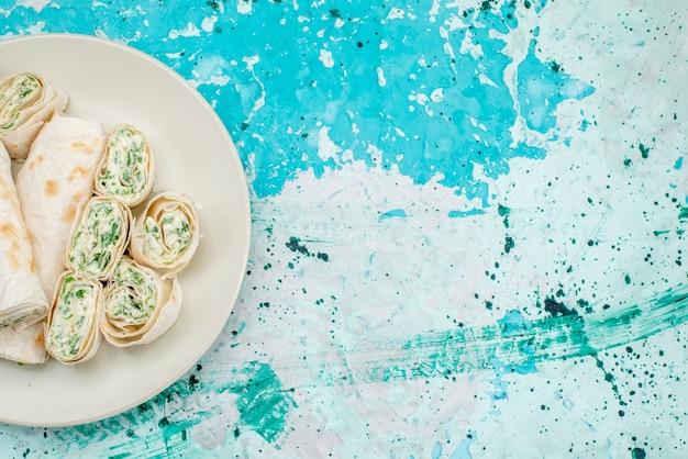 Draufsicht auf köstliche gemüsebrötchen ganz und in scheiben geschnitten auf hellblauem schreibtisch, lebensmittelmehlrolle gemüsesnack