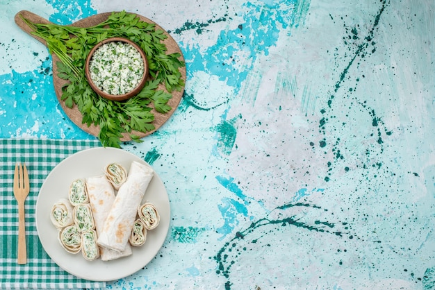 Draufsicht auf köstliche gemüsebrötchen ganz und in scheiben geschnitten mit gemüse und salat auf hellblauem gemüsesnack mit essensröllchen