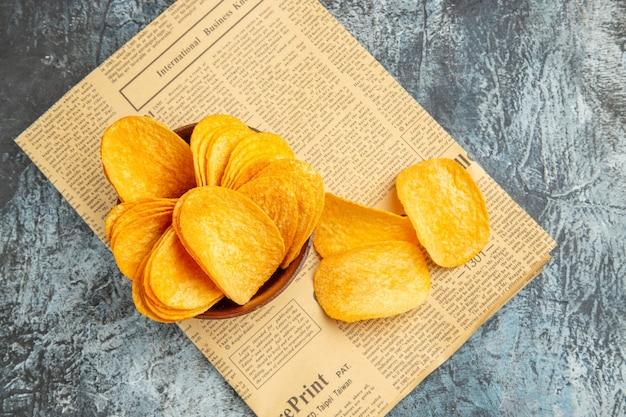 Draufsicht auf köstliche hausgemachte chips auf zeitung auf grauem tisch