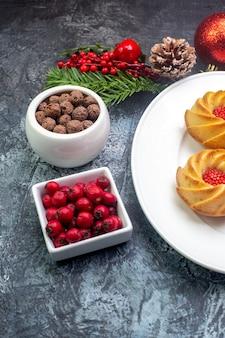 Draufsicht auf köstliche kekse auf einem weißen teller und neujahrsdekorationen geschenk cornel in kleiner topfschokolade auf dunkler oberfläche