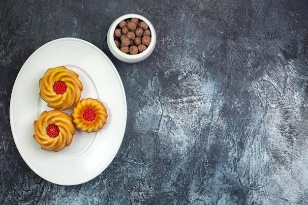Draufsicht auf köstliche kekse auf einem weißen teller und pralinen in einer schüssel auf dunkler oberfläche
