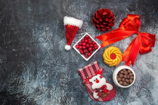 Draufsicht auf köstliche kekse und cornel-schokolade in weißen töpfen neujahrssocke rotes nadelbaum-kegel-rotes band auf der linken seite auf dunkler oberfläche