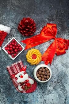 Draufsicht auf köstliche kekse und kornel auf einem weißen teller neujahrssocke roter nadelbaumkegel rotes band weihnachtsmann-hut auf dunkler oberfläche
