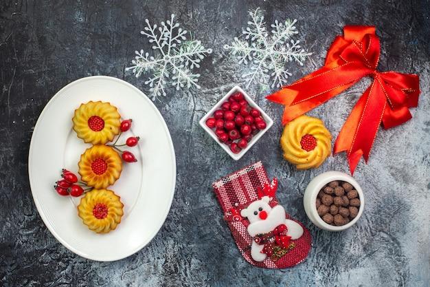 Draufsicht auf köstliche kekse und kornel auf einem weißen teller neujahrssocke rotes nadelbaum-kegel-rotes band auf dunkler oberfläche