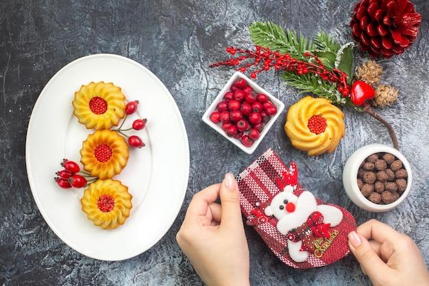 Draufsicht auf köstliche kekse und kornel auf einem weißen teller neujahrssocken roter koniferenkegel auf dunkler oberfläche
