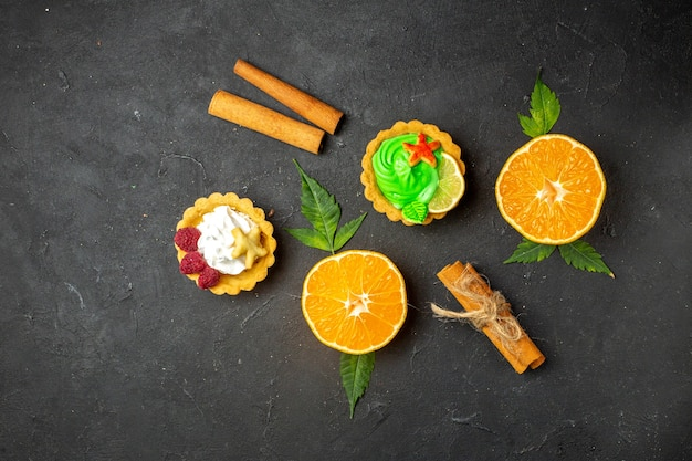 Draufsicht auf köstliche kekse, zimtlimetten und halbgeschnittene orangen mit blättern auf dunklem hintergrund