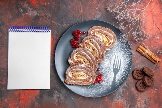 Draufsicht auf köstliche keksröllchen mit keksen auf dunkler oberfläche